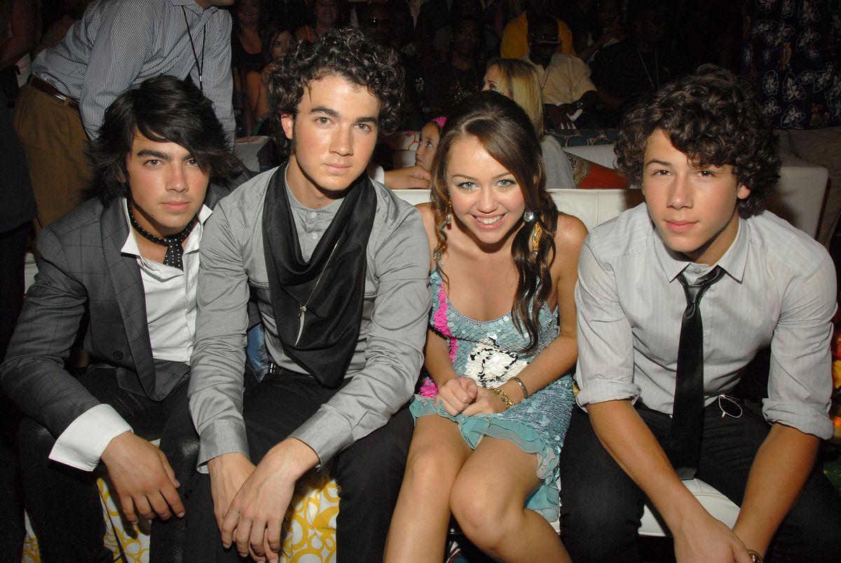 (EXCLUSIVE, Premium Rates Apply) UNIVERSAL CITY, CA - AUGUST 26:  Musicians Kevin Jonas, Joe Jonas and Nick Jonas of the Jonas Brothers with singer/actress Miley Cyrus backstage at the 2007 Teen Choice Awards at Gibson Amphitheater on August 26, 2007 in Universal City, California.  (Photo by Kevin Mazur/WireImage)