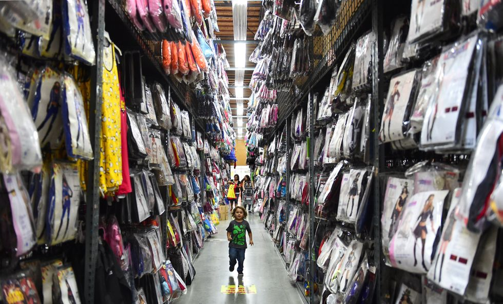 A child runs down the aisle ahead of his mother shopping for costumes at the Halloween Club store in Montebello, California on October 16, 2014 ahead of the annual end of the month tradition on October 31. Halloween is one of the fastest growing consumer spending holidays in America as people buy not only costumes for the festivities but all kinds of decorations as well for their homes to create a spooky atmosphere for the children out trick or treating. AFP PHOTO / Frederic J. BROWN (Photo credit should read FREDERIC J. BROWN/AFP/Getty Images)