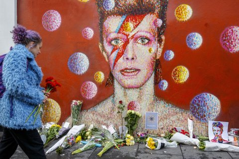 LONDON, UNITED KINGDOM - JANUARY 11: David Bowie fans pay their respects at his mural in Brixton, where he was born, in London, England on January 11, 2016. Music legend David Bowie died when he was 69 years old, after suffering from cancer. (Photo by Tolga Akmen/Anadolu Agency/Getty Images)