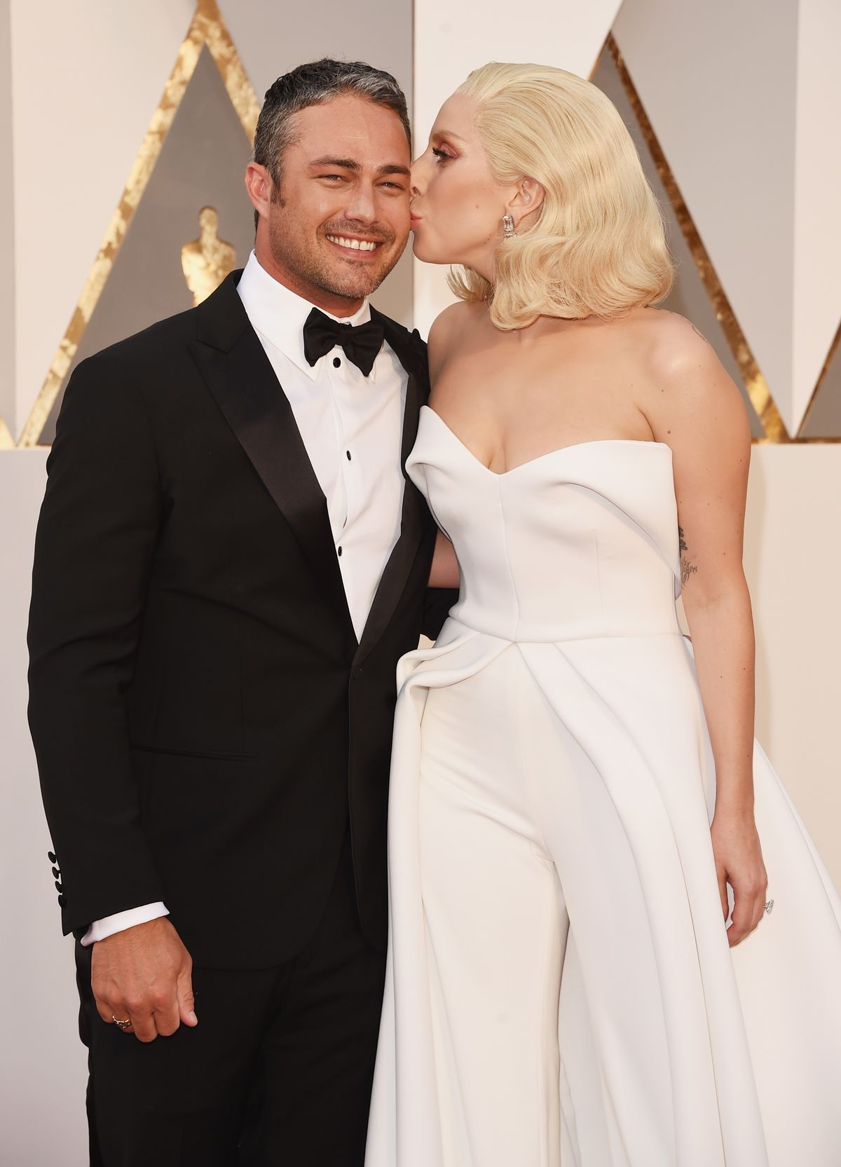 HOLLYWOOD, CA - FEBRUARY 28: Recording artist Lady Gaga (R) kisses actor Taylor Kinney at the 88th Annual Academy Awards at Hollywood & Highland Center on February 28, 2016 in Hollywood, California. (Photo by Jason Merritt/Getty Images)