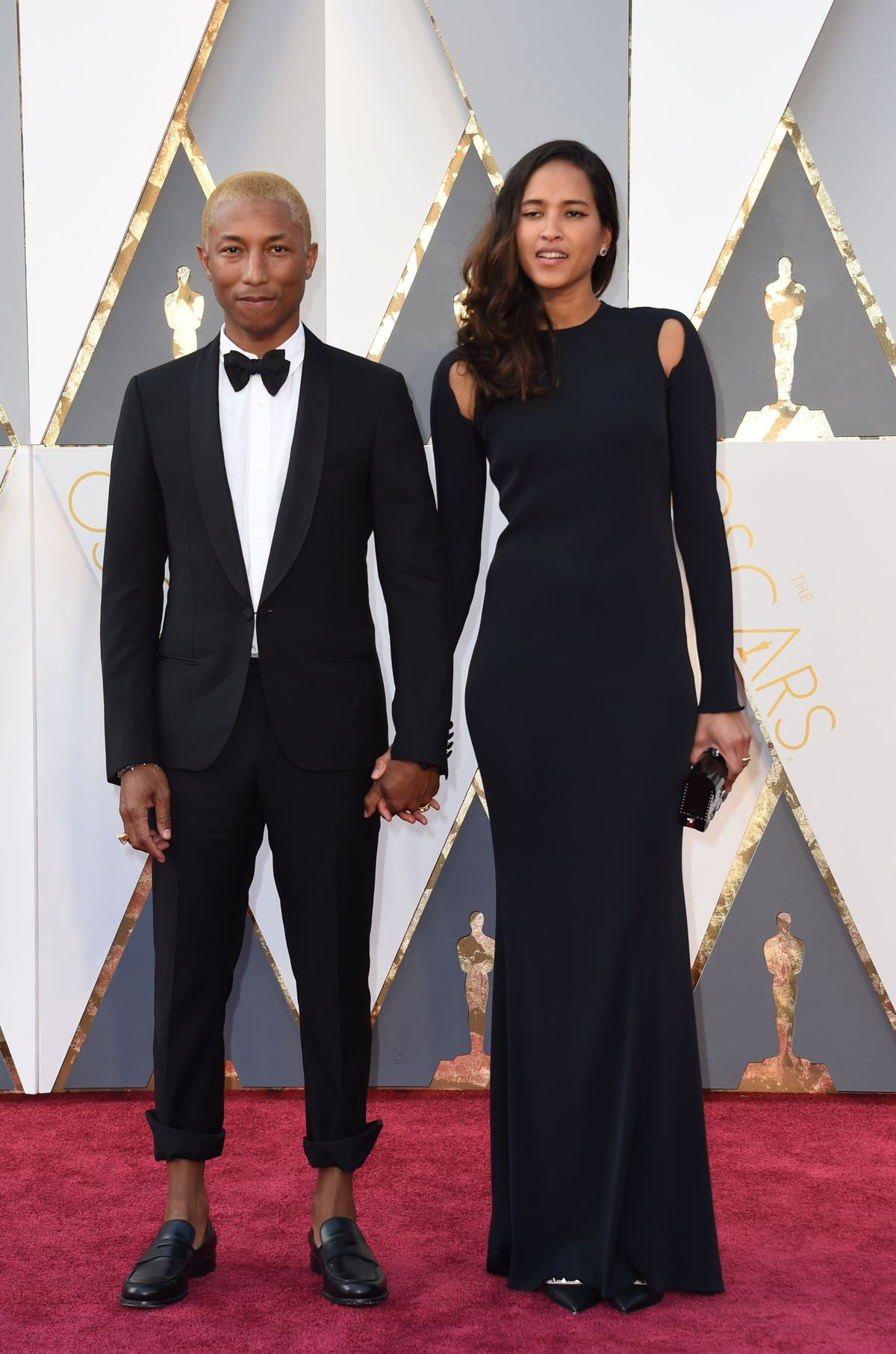Singer Pharrell Williams and Helen Lasichanh arrive on the red carpet for the 88th Oscars on February 28, 2016 in Hollywood, California. AFP PHOTO / VALERIE MACON / AFP / VALERIE MACON (Photo credit should read VALERIE MACON/AFP/Getty Images)